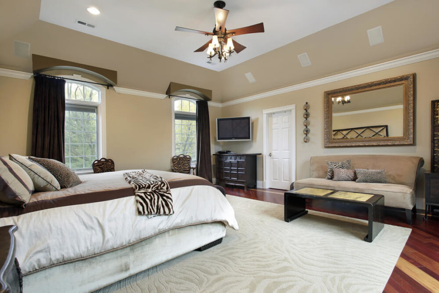 A Spacious Master Bedroom With A Deep Tray Ceiling And A Large Ceiling Fan.  Against