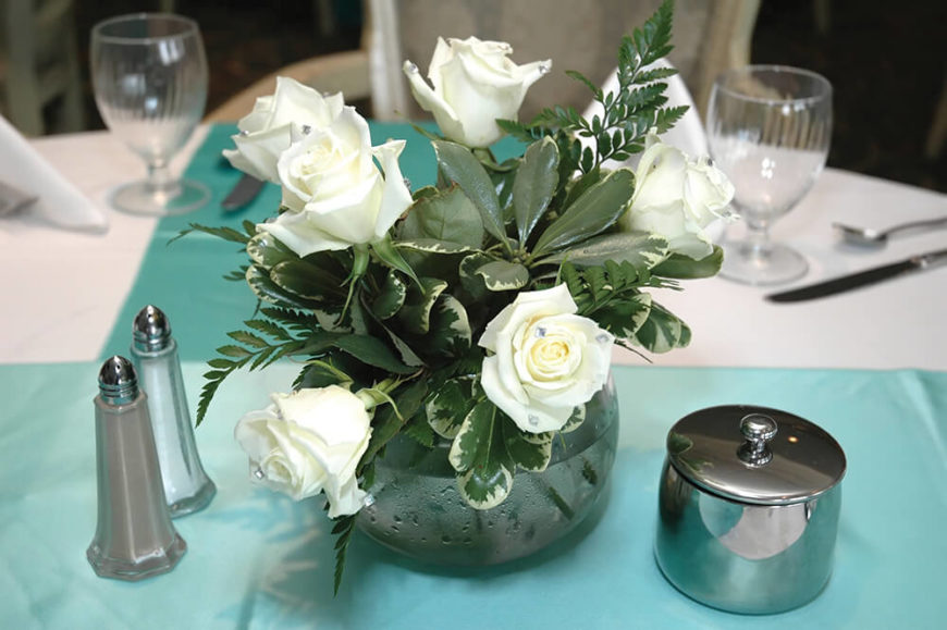 A Small And Delicate Floral Arrangement Consisting Of White Roses Tucked Into Glass Vase With