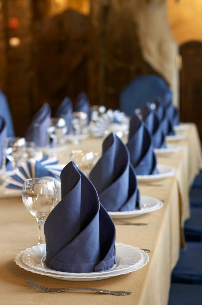 a beautiful simple arrangement of white scalloped edge dishes paired with elegantly folded navy napkins