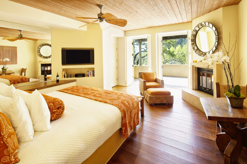 this light and airy master bedroom features rich hardwood flooring a