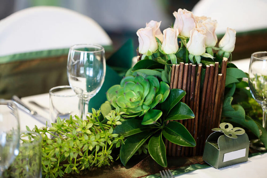 A Longer Floral Arrangement With Base Of Succulents Leading Up Into Vase White