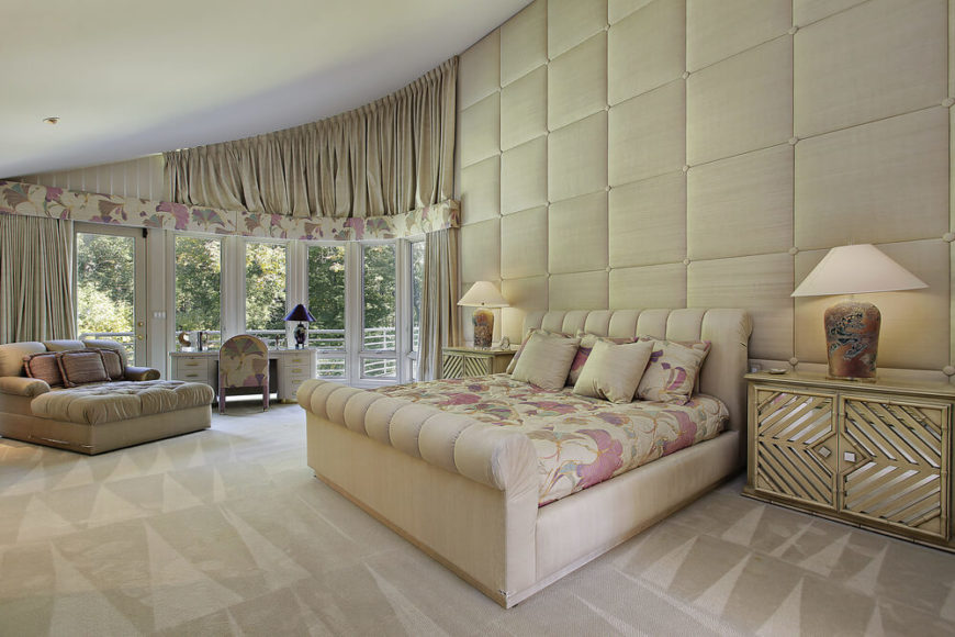 A Curved, Spacious Master Bedroom With An Upholstered Accent Wall, Bed, And  An