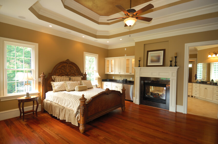 An Elegant Master Bedroom With Rich Red Hardwood Floors, A Dual Sided  Fireplace Shared