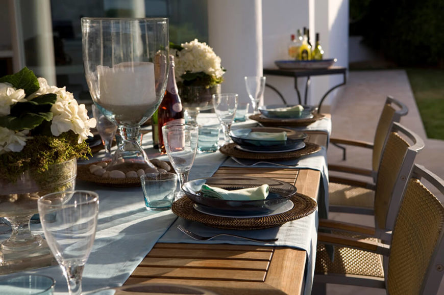 a table set for an outdoor dinner party light blue placemats match the table runner - Dining Room Table Settings