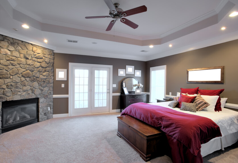 A Luxurious Master Bedroom With Soft Carpet, French Doors To A Patio, A  Custom