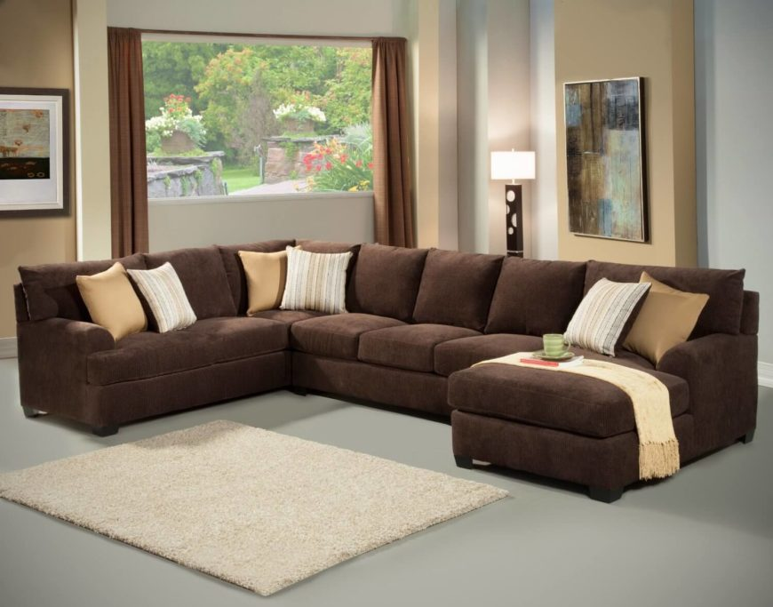 A Large Chocolate Sectional Sits Atop Matte Gray Floor An Ivory Area Rug Breaks