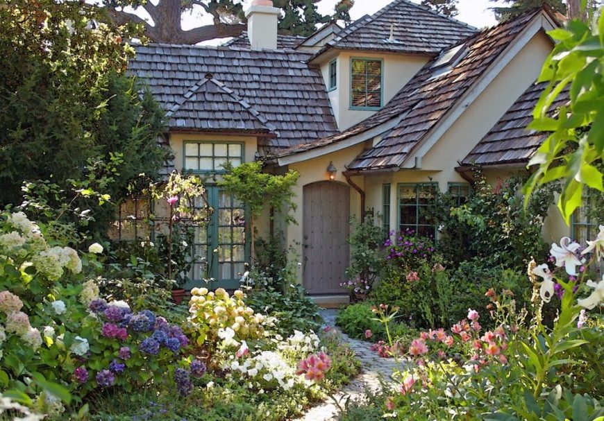 Cedar shingles are perfect for that rustic cottage look. This home is flourishing with bright flowers and country themed wood– including the natural wooden shingles.