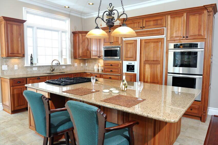 expansive island in this kitchen features a light granite countertop ...