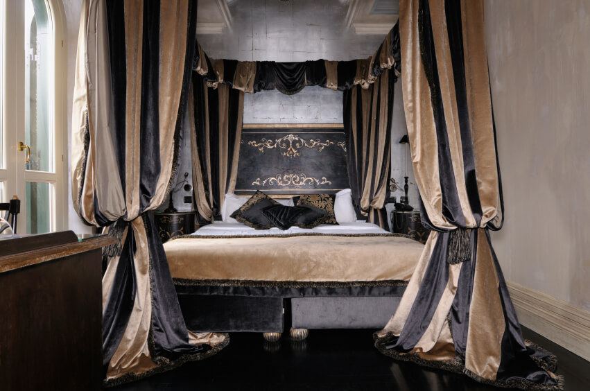 The incredible luxury of this bed is centered on the thick, gathered velvet  curtains.