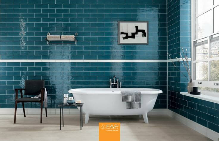 the bathtub in this unique bathroom pops against the polished turquoise walls the color