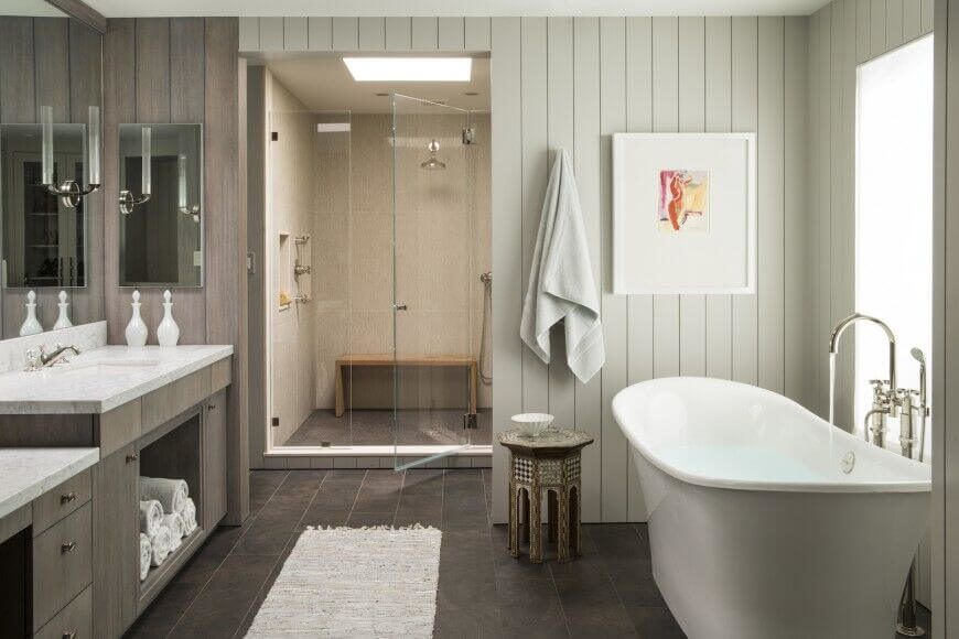 this chic bathroom has a neutral color scheme and a rich dark tiled floor