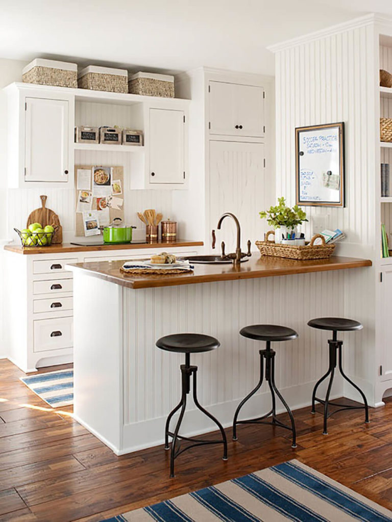 wooden counters and the addition of thickly woven accent baskets are wonderful neutral touches against this - Small Cottage Kitchen