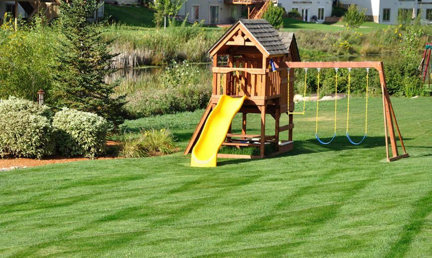 Backyard Playground Sets Part - 33: A Wooden Play Area With A Slide And Swingset. Below The Cabin Area Is A
