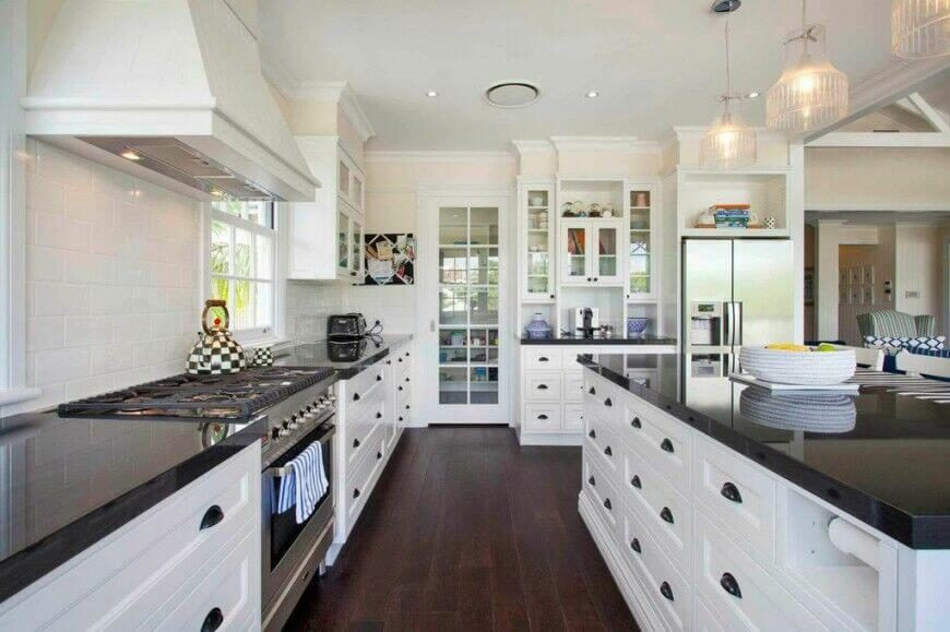 wonderful Kitchen White Cabinets Black Granite #2: This gorgeous contemporary kitchen utilizes dark granite counter tops and  wood flooring to break up the