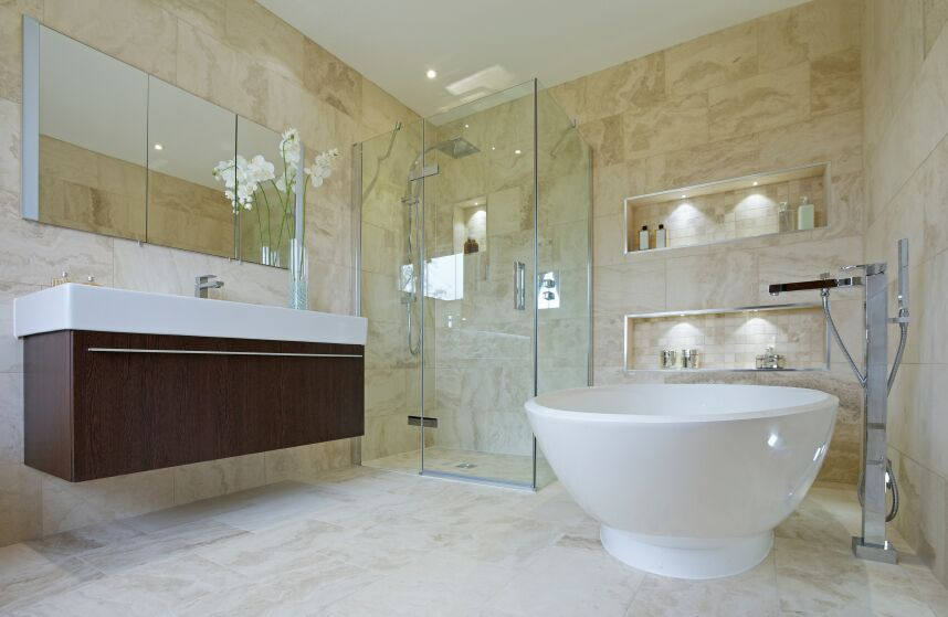 this bathroom is tiled entirely in beige and includes a corner glass enclosed walk