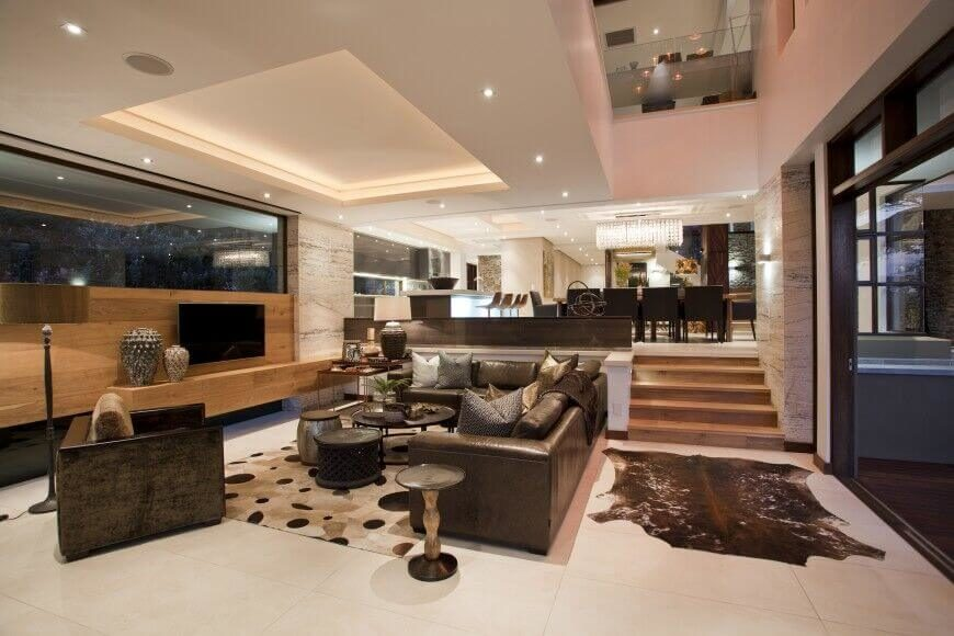 A leather sectional sofa complements the cowhide rug and other dark brown  elements of this modern. 22 Sophisticated Living Rooms with Leather Furniture  DESIGNS
