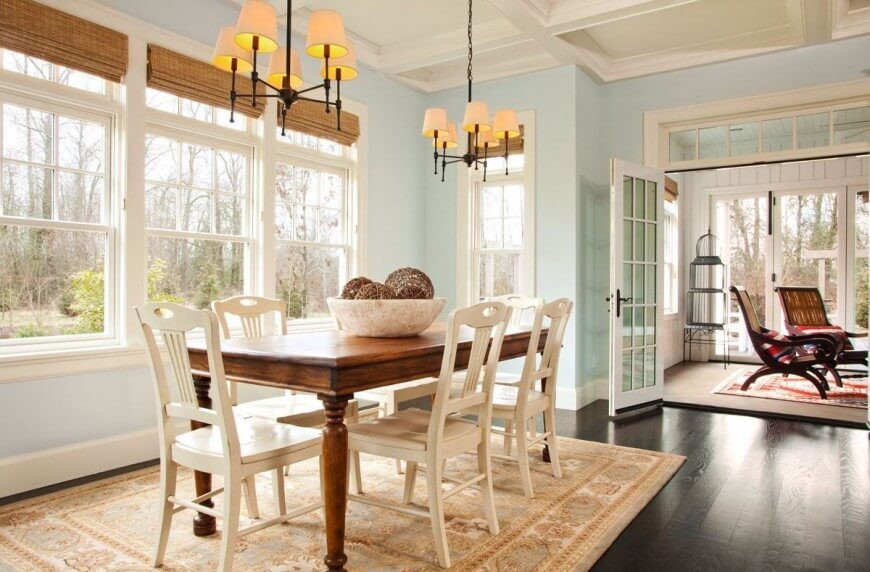 this coastal contemporary dining room features rich dark hardwood floors and breezy french doors that lead