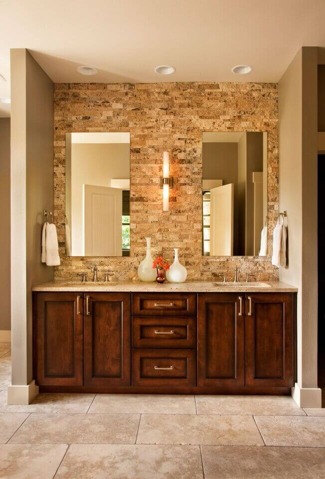 A rugged brick wall behind the counter in this bathroom provides a lot of  texture,