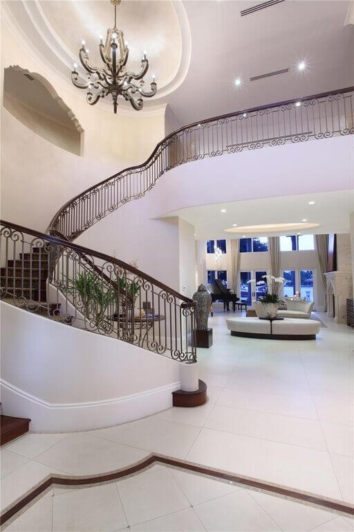 This contemporary foyer has an incredible spiral staircase that leads to a hallway overlooking the foyer and living room. The foyer continues directly into the formal living room, and is namely for show.
