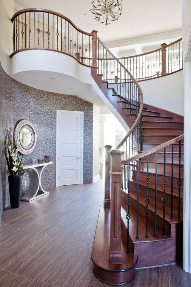 A more unique foyer featuring speckled walls, wood-look tile floors, and an all-wood spiral staircase.
