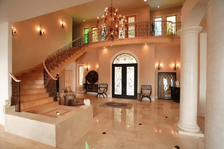Viewed from the rear of the foyer towards the front door, we see the balcony overlooking the tile foyer, and the immense chandelier hanging from the tall ceilings.