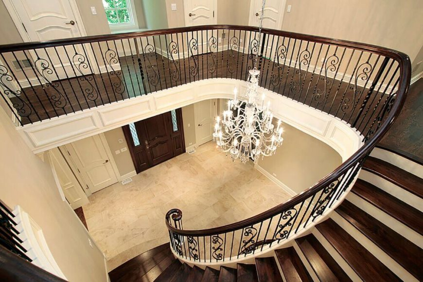 a view from the top of the staircase down the rich polished stairs and into the - Foyer Tile Design Ideas