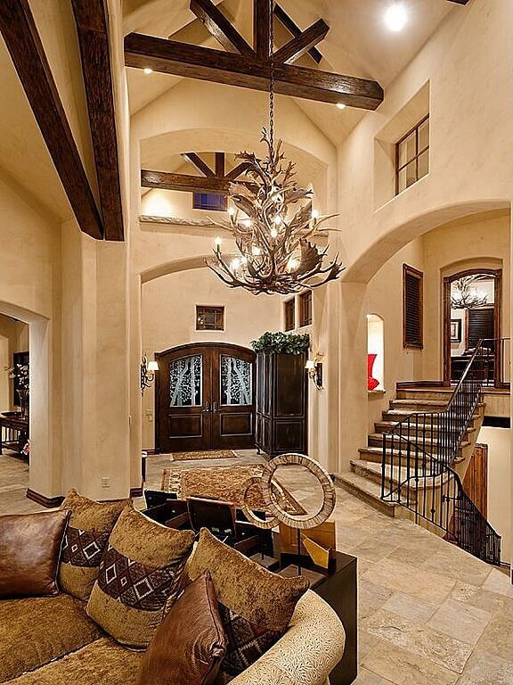 Our final image is that of an open-concept foyer that connects to a great room and two staircases. An enormous chandelier made of antlers hangs from the arched ceilings, passing by the wooden cross beams in the home.
