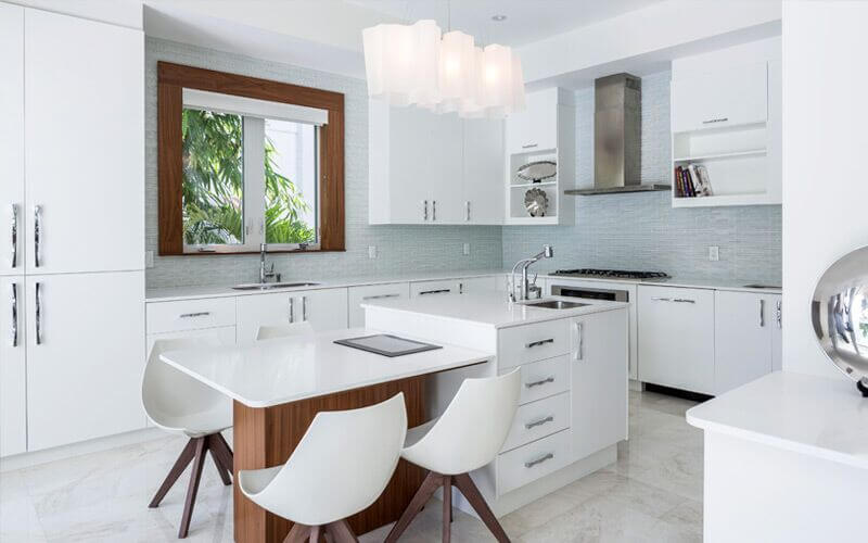 A White Modern Kitchen With A Light Gray Glass Mosaic Tile Backsplash And A  Small Island