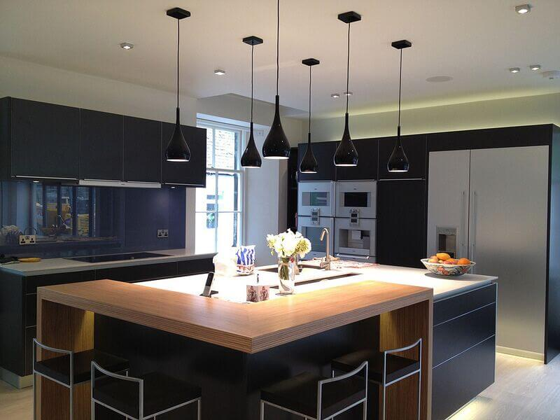 Dark kitchen with pendant lights and a large island.