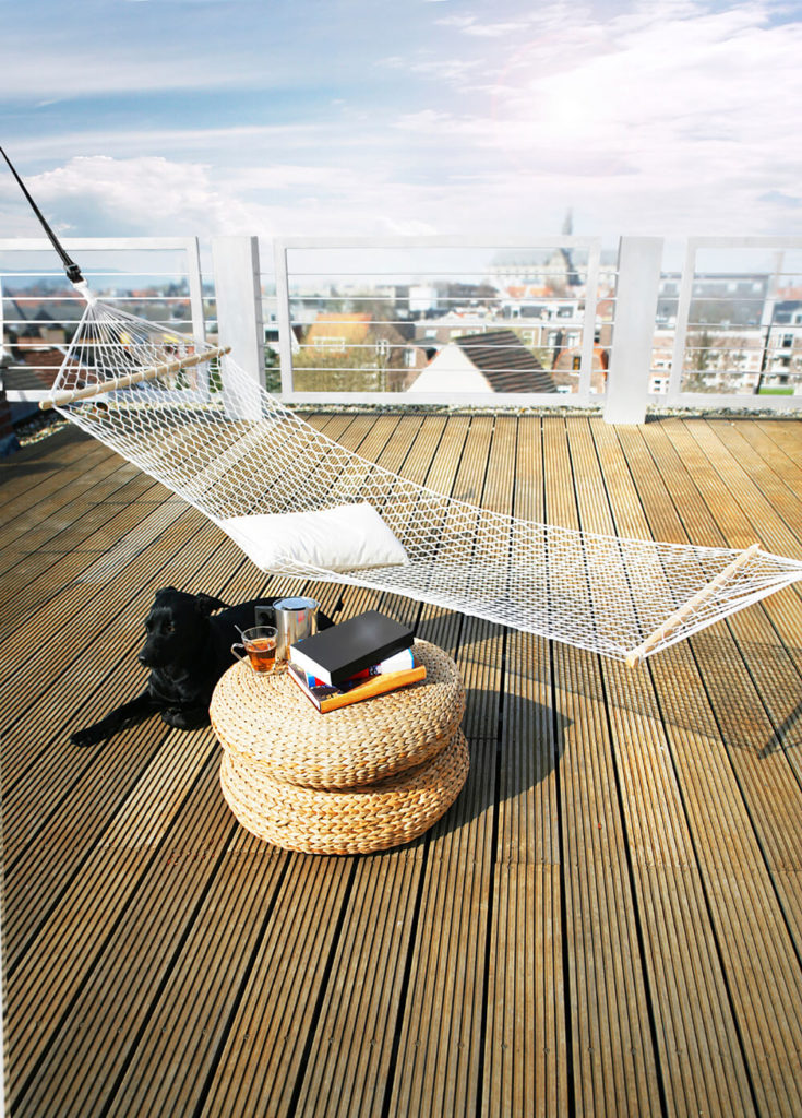 A Private Rooftop Patio With Textured Plank Decking, A Wicker End Table,  And A