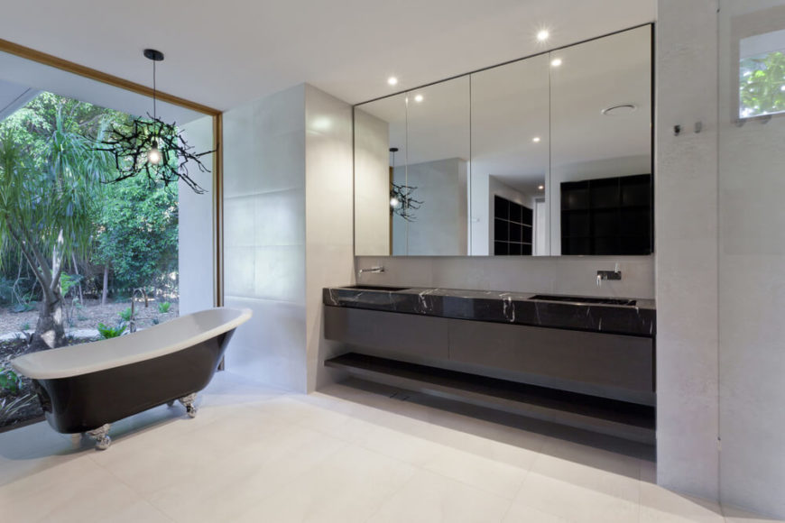A Fine Marble Counter Is Home To Two Sinks In Front Of A Large Mirror