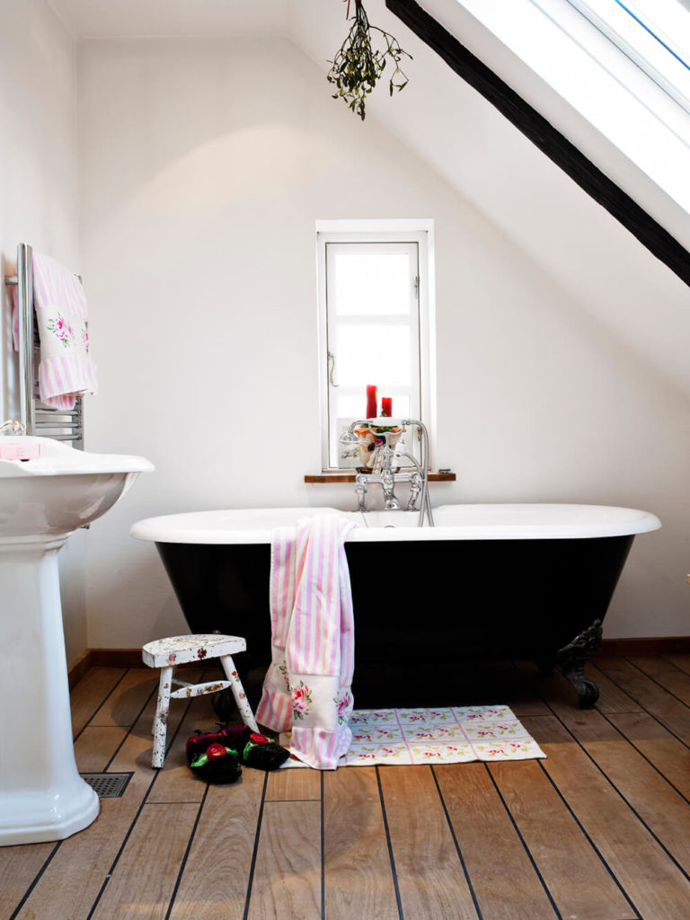 A Simple And Modest Space, This Bathroom Features A Black Clawfoot Tub  Sitting Atop A