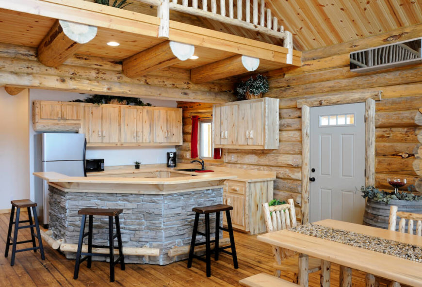 Wood log cabin style kitchen with a loft and stone accents the island