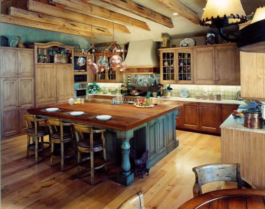 A Rustic Kitchen With Exposed Wooden Beams, Distressed Cabinetry And  Island, And Copper Accents