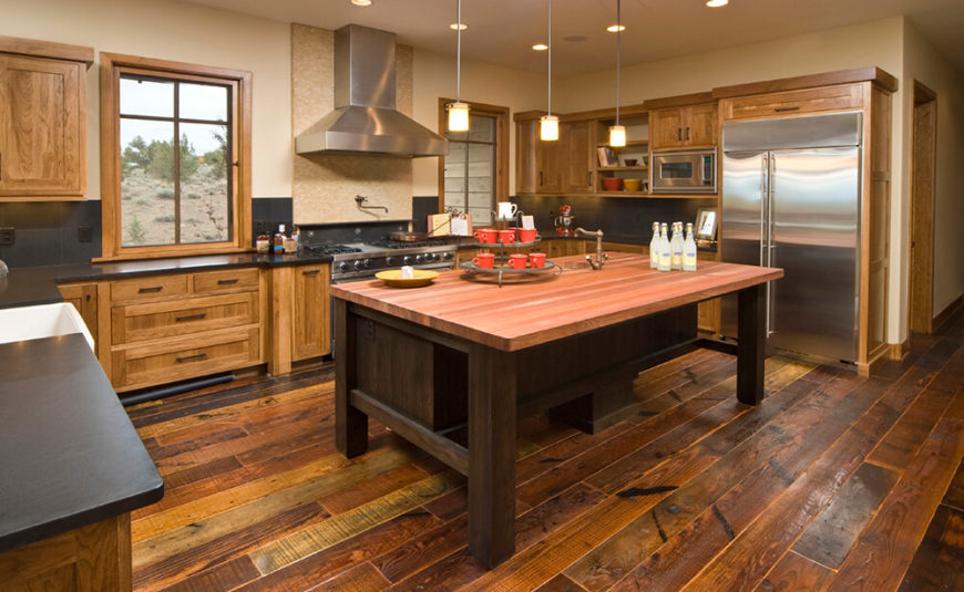 A rustic wooden kitchen with multi tonal wood floors, a butchers block  island, and