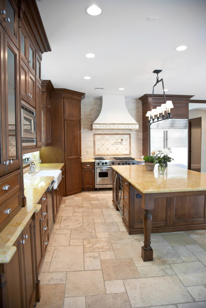 A light beige stone tile floor supports rich dark stained wood cabinetry  and island in this. 25 of Our Very Best Traditional Kitchen Designs  FANTASTIC PICTURES