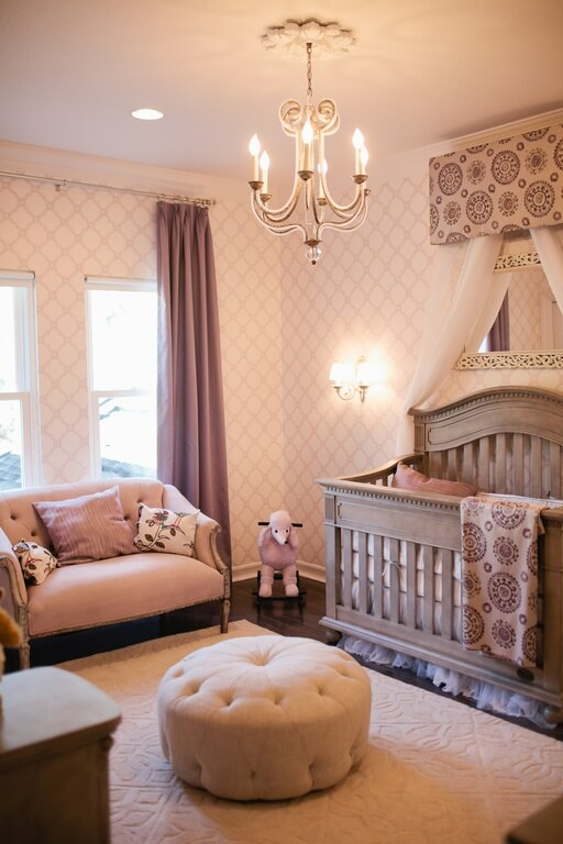 An elegant nursery with a princess-style canopy above the wooden crib, a chandelier, and wallpapered walls. At the center of the design is a comfy-looking button-tufted pouf.