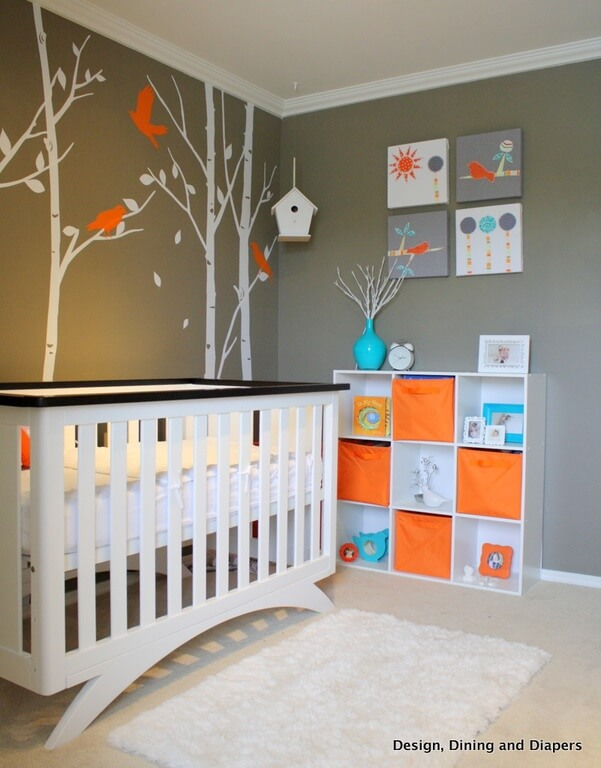 A brightly colored forest-themed nursery with accents of orange and bright blue. Canvas art is arranged above the open shelving unit across from the black and white crib. Vinyl decals are used to create the forest motif behind the crib.