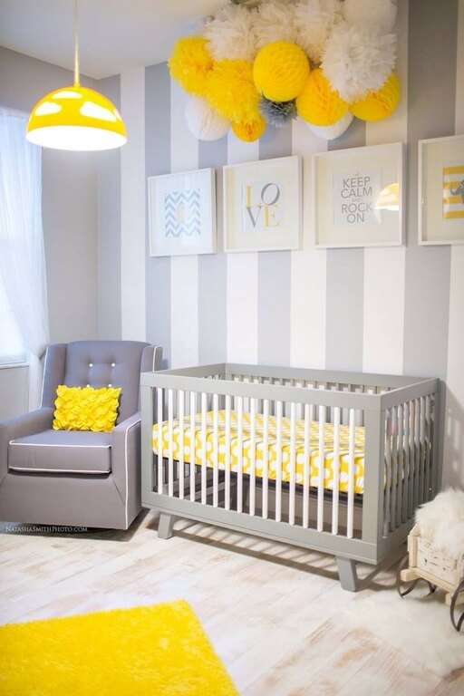 A more contemporary nursery in gray accented by a sunny, bold yellow. One wall is accented with white stripes and decorated with a series of framed prints in gray and yellow. A pom-pom decoration at the top of the wall ties the space together perfectly.