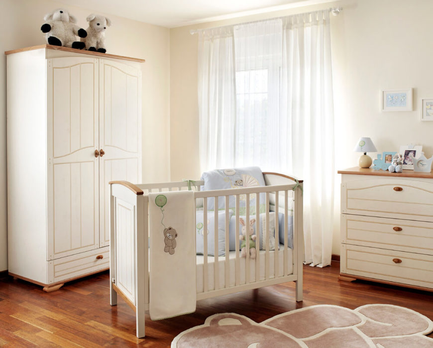 Cream teddy bear nursery with hardwood flooring and breezy curtains.