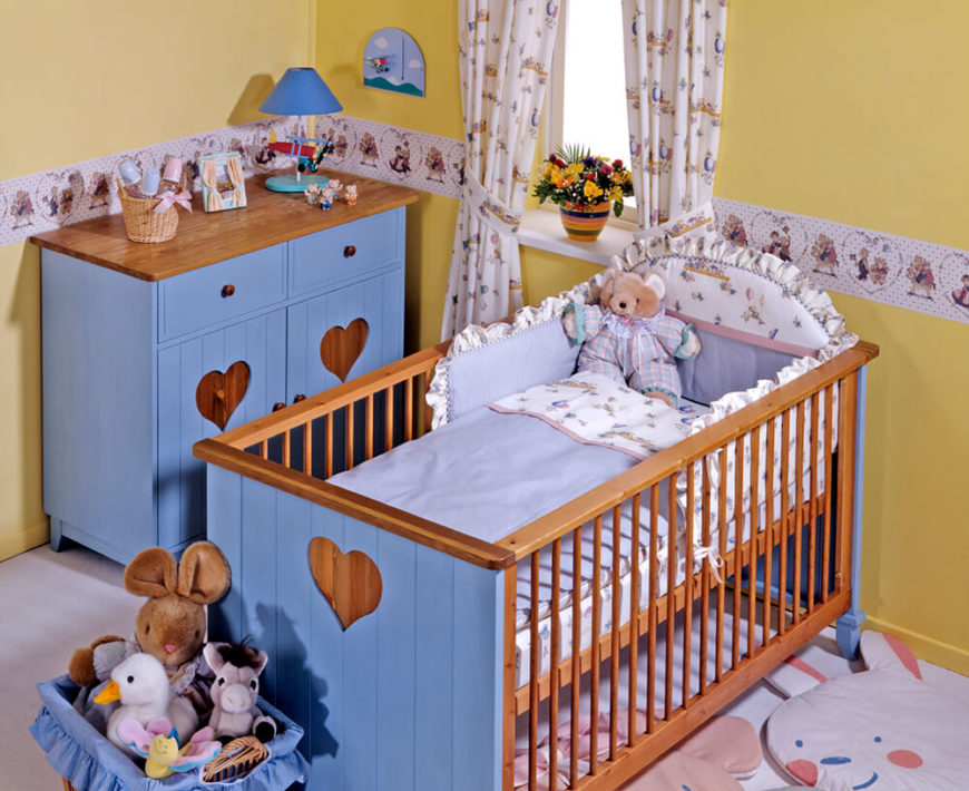 A sweet nursery in yellow and blue with a teddy bear border and curtains. Animal rugs lay near the ruffled crib. Both the crib and the small dresser nearby have heart-cutouts on the sides.