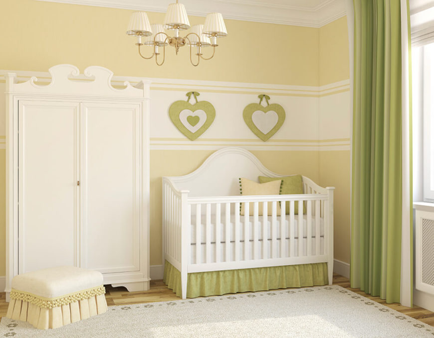 An elegant nursery in pastel green and white with a chandelier, bamboo flooring, and crown molding. On the wall above the crib are two heart-shaped hanging ornaments.