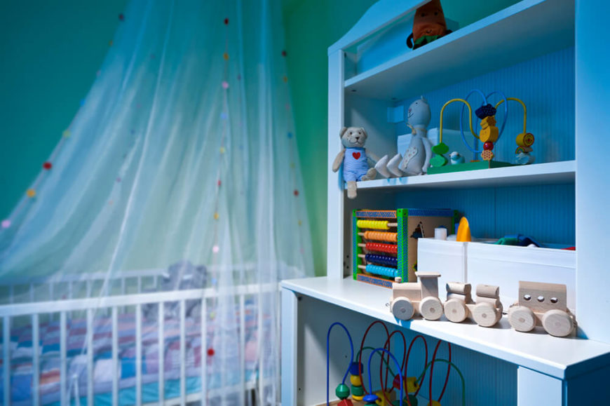 A lovely traditional style nursery with a canopy over the white crib and a large shelving unit next to it serving as storage for toys.