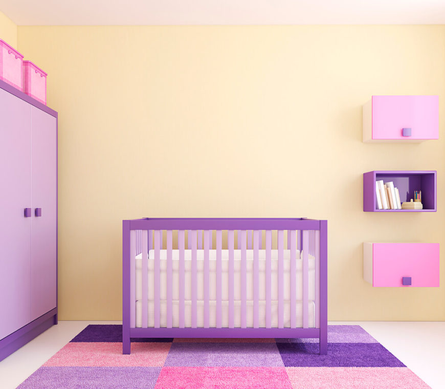 A bold modern nursery with floating shelving, a purple and lavender armoire, and a colorful checkered rug. The walls are in a pastel yellow, contrasting softly with the pinks and purples of the furniture and accents