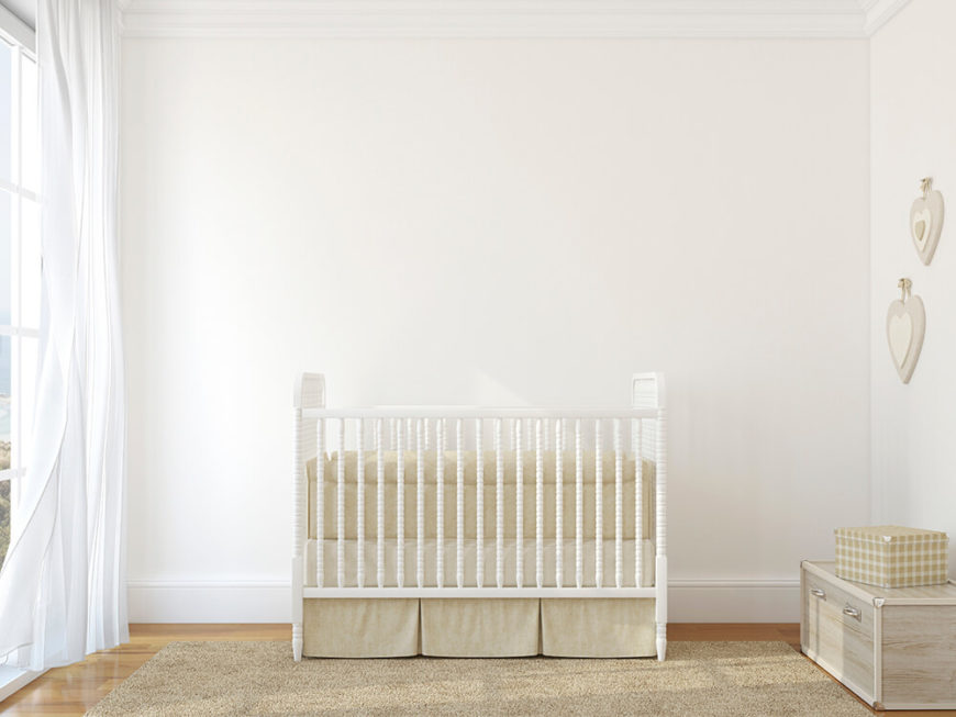 A sleek, airy white nursery with cream accessories and floor to ceiling windows. Perfect for those who love modern design, while not sacrificing comfort.