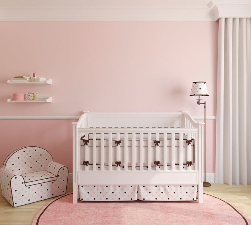 A traditionally feminine pink nursery with polka dots in brown, white and pink. A chair rail separates the darker pink lower walls from the more pastel upper portion of the walls.