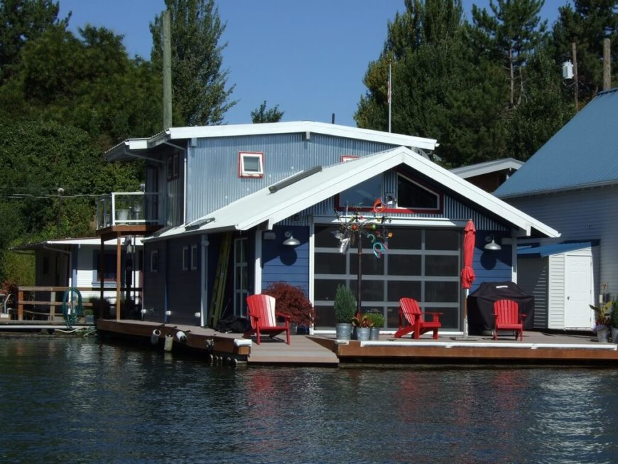 A very large and luxurious permanently moored house boat in a gorgeous blue. Red trim and accents stand out against the large window on the front.