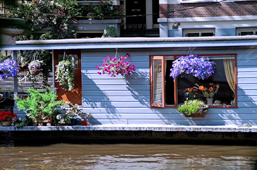 A single story houseboat with a wealth of colorful hanging baskets, window boxes, and containers of plants all along the porch.