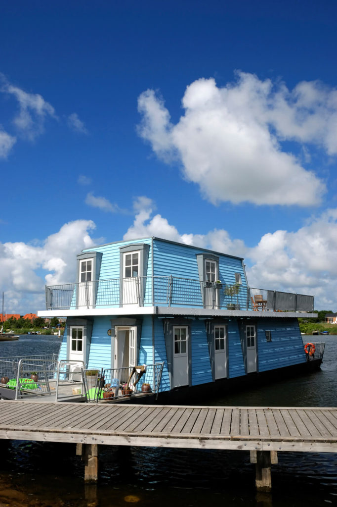 A baby blue two-story trapezoidal houseboat with a large variety of decks and balconies, perfect for the owners to sit and enjoy the breeze.