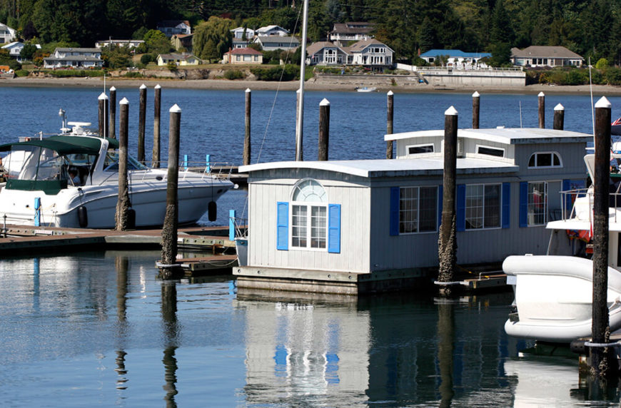 This houseboat is moored at a marina, and resembles a pre-fabricated home placed on top of a large raft.